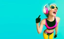 Muchacha atractiva de DJ de la moda en ropa brillante en un fondo azul Imagen de archivo