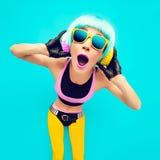 Muchacha atractiva de DJ del partido en ropa brillante en un fondo azul l Fotografía de archivo