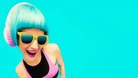 Muchacha atractiva de DJ del partido en ropa brillante en un fondo azul l Imágenes de archivo libres de regalías
