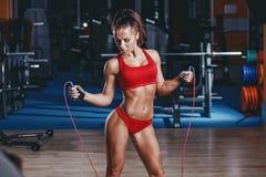 Muchacha atractiva de la aptitud con la figura deportiva sana con la cuerda que salta en gimnasio Imagen de archivo