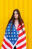 Muchacha atractiva de la muchacha en una chaqueta negra cubierta en bandera de los E.E.U.U. Imagen de archivo