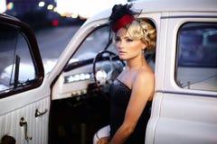 Muchacha atractiva de la moda que se sienta en coche viejo Foto de archivo