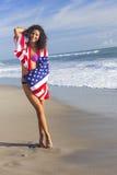 Muchacha atractiva de la mujer joven en bandera americana en la playa Foto de archivo libre de regalías