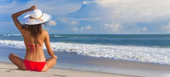 Muchacha atractiva de la mujer que sienta el sombrero y el bikini de Sun en la playa imagenes de archivo