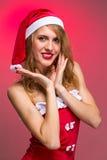 Muchacha atractiva de la Navidad en el sombrero de santa en un rojo Imagen de archivo libre de regalías
