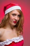 Muchacha atractiva de la Navidad en el sombrero de santa en un rojo Foto de archivo