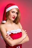 Muchacha atractiva de la Navidad en el sombrero de santa en un rojo Fotos de archivo