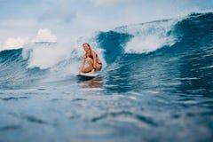 Muchacha atractiva de la persona que practica surf en el paseo de la tabla hawaiana en ola oceánica Mujer en el océano durante pr Imagen de archivo libre de regalías