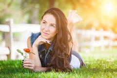 Muchacha atractiva de la raza mixta que sostiene el retrato de la flor que pone en Gra Imagen de archivo