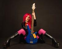 Muchacha atractiva de la roca que se sienta con la guitarra baja Fotografía de archivo libre de regalías