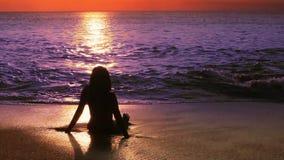 muchacha atractiva de la silueta misteriosa en la playa durante puesta del sol almacen de metraje de vídeo