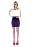 Muchacha atractiva de las ventas que sostiene el ordenador portátil Imagen de archivo