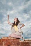 Muchacha atractiva de moda que presenta en la pared de ladrillo vieja en la parte posterior del cielo Foto de archivo