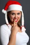 Muchacha atractiva de santa con el dedo en boca Fotos de archivo