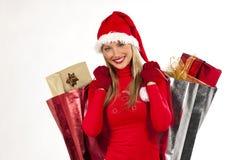 Muchacha atractiva de Santa con los bolsos de los presentes Foto de archivo