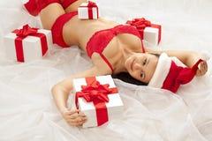 Muchacha atractiva de santa con los rectángulos de regalo Imagen de archivo libre de regalías