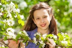 Muchacha atractiva del adolescente con las flores blancas de la pera Imagen de archivo