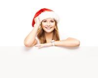 Muchacha atractiva del adolescente en un sombrero de la Navidad con una cartelera en blanco Imagen de archivo libre de regalías