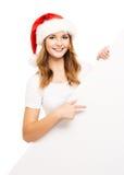 Muchacha atractiva del adolescente en un sombrero de la Navidad con una cartelera en blanco Fotos de archivo