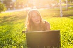 Muchacha atractiva del adolescente que se divierte con el ordenador portátil al aire libre Fotos de archivo