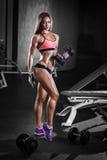 Muchacha atractiva del atleta con una pesa de gimnasia en el gimnasio Imagenes de archivo