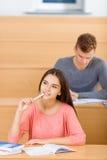 Muchacha atractiva del estudiante profundamente en pensamientos Foto de archivo libre de regalías