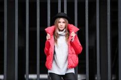 Muchacha atractiva del inconformista en chaqueta roja cerca de la cerca del metal Fotos de archivo