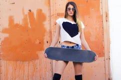 Muchacha atractiva del patinador que sostiene el monopatín en sus manos Foto de archivo libre de regalías