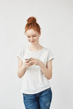 Muchacha atractiva del pelirrojo con las pecas que sonríe mirando el teléfono Imágenes de archivo libres de regalías