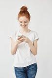 Muchacha atractiva del pelirrojo con las pecas que sonríe mirando el teléfono Fotografía de archivo libre de regalías