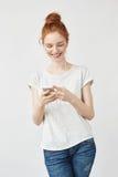Muchacha atractiva del pelirrojo con las pecas que sonríe mirando el teléfono Fotos de archivo