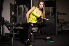 Muchacha atractiva deportiva con los grandes músculos abdominales en ropa de deportes negra Foto de archivo