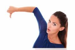 Muchacha atractiva en camisa azul con el pulgar abajo Imagen de archivo