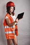 Muchacha atractiva en casco de seguridad usando panel táctil de la tableta Foto de archivo libre de regalías