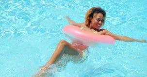 Muchacha atractiva en el bikini que descansa en la piscina