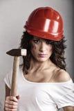 Muchacha atractiva en el casco de seguridad que sostiene la herramienta del martillo Fotos de archivo libres de regalías