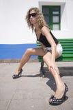 Muchacha atractiva en el miniskirt que se sienta en la calle Imagen de archivo