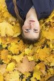 Muchacha atractiva en el parque del otoño que pone en las hojas amarillas Fotografía de archivo libre de regalías