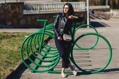 muchacha atractiva en el parque soleado cerca del estacionamiento del ciclo imagen de archivo