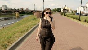 Muchacha atractiva en gafas de sol en la calle que camina y que come el helado Leva constante almacen de video