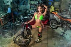 Muchacha atractiva en garaje con los neumáticos de la bici imagen de archivo