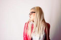 Muchacha atractiva en la chaqueta de cuero roja que presenta en estudio Foto de archivo libre de regalías