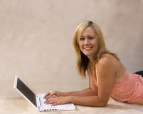 Muchacha atractiva en la computadora portátil Foto de archivo