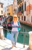 Muchacha atractiva en la costa de un canal estrecho en Venecia Imágenes de archivo libres de regalías