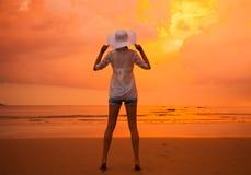 Muchacha atractiva en la playa durante puesta del sol Foto de archivo libre de regalías