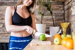 Muchacha atractiva en la ropa de deportes que prepara un desayuno sano en la cocina antes de entrenar, cortando la fruta y la fab foto de archivo