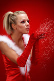 Muchacha atractiva en nieve que sopla del paño de santa de las manos. Foto de archivo libre de regalías