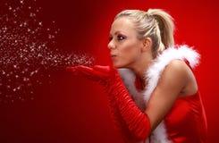 Muchacha atractiva en nieve que sopla del paño de santa de las manos. Fotos de archivo libres de regalías