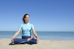 Muchacha atractiva en a piernas cruzadas actitud del loto de la yoga en la playa Fotografía de archivo libre de regalías