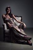 Muchacha atractiva en silla vieja foto de archivo libre de regalías